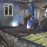 Сотрудники производства варят металлический каркас блок-контейнера